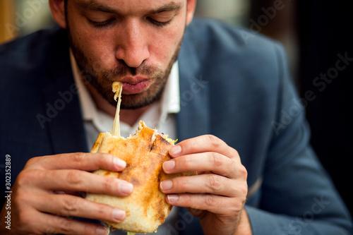 Foto op Aluminium Kruidenierswinkel Businessman eating junk food sandwich