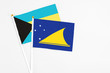 Tokelau and Bahamas stick flags on white background. High quality fabric, miniature national flag. Peaceful global concept.White floor for copy space.