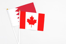 Canada And Bahrain Stick Flags On White Background. High Quality Fabric, Miniature National Flag. Peaceful Global Concept.White Floor For Copy Space.