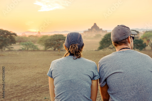 Back wiew of tourists admire and take photography while the sun sets at the anci Canvas Print