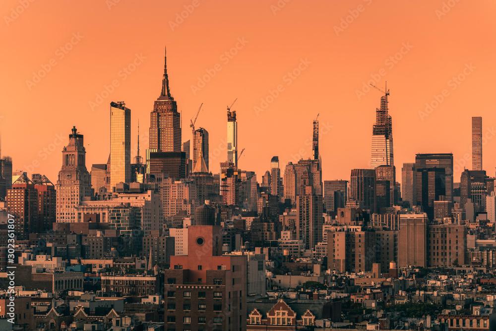 Fototapeta Sunset above Manhattan skyscrapers, New York City. Light effect applied