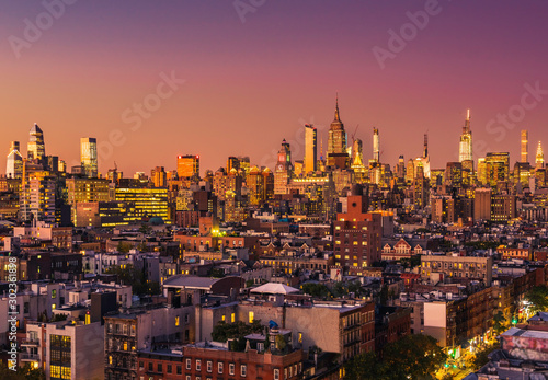 Fototapeten New York Manhattan tall buildings during orange sunset. New York City panorama. Sky made up with orange tone
