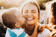 Beautiful young mother laughing with closed eyes while her son is embracing her neck and kissing her cheek outdoor against sunset.