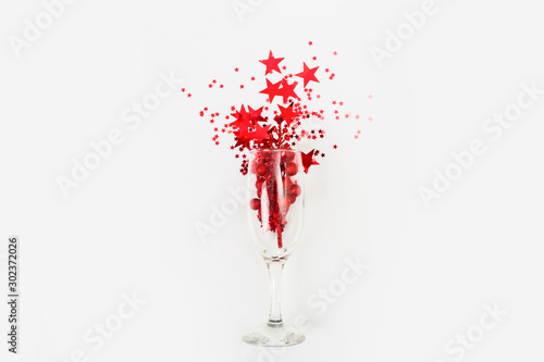 Poster de jardin Alcool Confetti in the form of stars poured glasses of champagne on a white background. View from above.