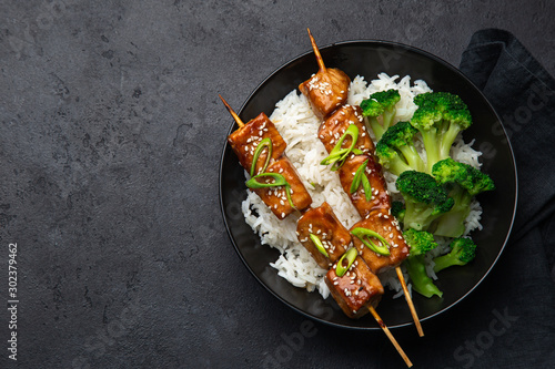 Photo Teriyaki salmon skewers with rice and broccoli on black plate