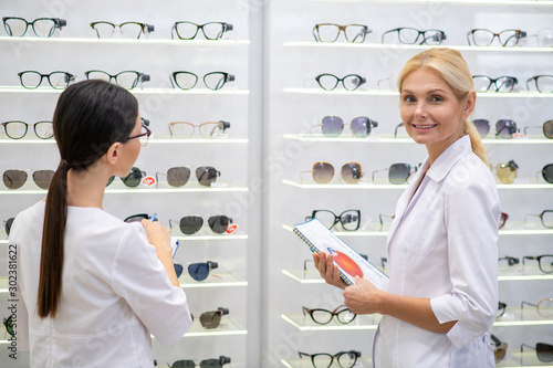 Two ophthalmologists wearing white coats standing in optical store