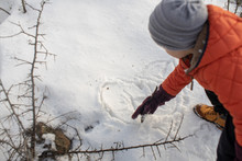 Toddler Boy Draws A Shape Of Heart In The Snow With A Wooden Stick