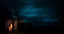 Lantern With Candle In Front Of Dark Background With Snowflakes