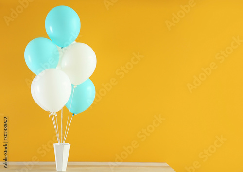 Fotomural  Air balloons with box on table against color background