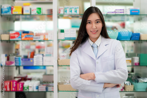 Photo  Confident Asian young female pharmacist with a lovely friendly smile standing with folded arms in the pharmacy drugstore