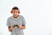 African-American Teenager Boy With Game Pad On White Brick Background