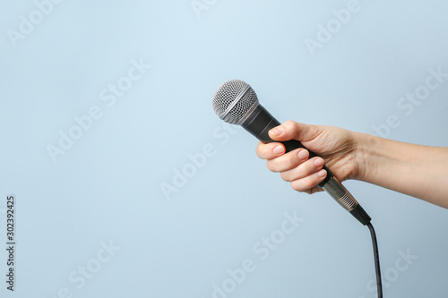 Obraz Female hand with microphone on color background - fototapety do salonu