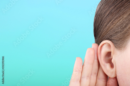 The girl listens attentively with her palm to her ear close-up, news concept Canvas Print