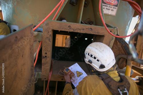 Fotografie, Tablou Certifies miner wearing fall body harness helmet protection holding gas test det