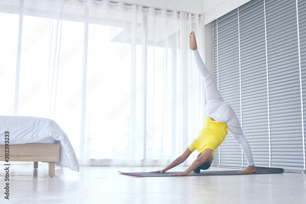 Fototapety, obrazy: Skinny woman wear yellow sport t-shirt practice yoga exercises for relaxing in the bedroom near the window, healthy lifestyle concept.