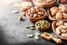 A Variety Of Nuts In Wooden Bowls From Top View. Walnuts, Cashew, Almond, Pistachio, Pecan, Hazelnut, Macadamia And Peanut Mix Selection. Healthy Fitness Super Food.