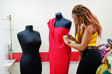 Young African Dressmaker Woman Designed New Red Dress On Mannequin At Tailor Office. Black Seamstress Women.
