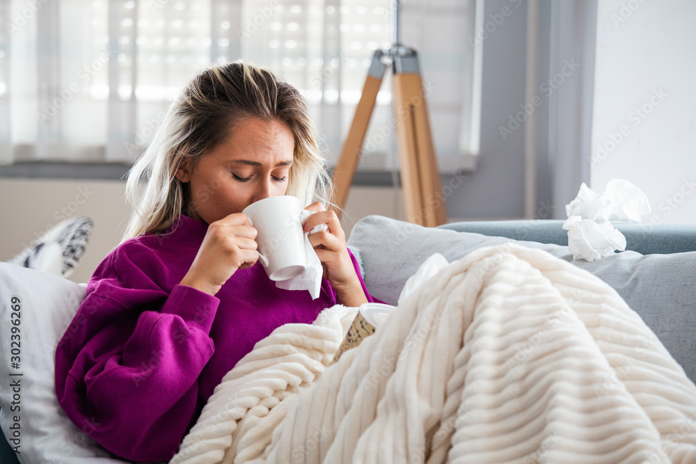 Fototapeta Cold And Flu. Portrait Of Ill Woman Caught Cold, Feeling Sick And Sneezing In Paper Wipe. Closeup Of Beautiful Unhealthy Girl Covered In Blanket Wiping Nose. Healthcare Concept. High Resolution