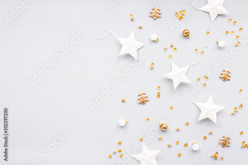 Fototapeta Gold and white christmas decoration on pastel blue background, flat lay, top view obraz na płótnie