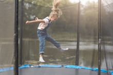 Full Length Photo Of Happy Girl Jumping High On Trampoline In Park, Blonde Female Chicd With Ponytail Wearing White Shirt And Denim Overalls, Kid Spending Time In Open Air, Having Fun Outdoor.