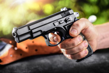 A Man Is Holding A Hand Gun With Sunny Background. 9 Mm Police Pistol Gun Dangerous Weapon Close Up.
