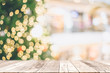 Leinwandbild Motiv Wooden table with space with Christmas tree and blurred light bokeh for mock up or montage your product advertisement.
