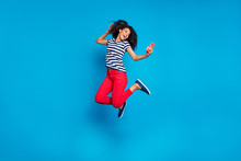 Full Length Body Size Turned Photo Of Cheerful Positive Cute Curly Wavy Pretty Girlfriend Jumping In Striped T-shirt Red Trousers Taking Selfie Isolated Vivid Blue Color Background