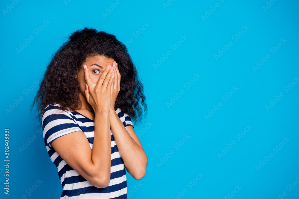 Fototapeta Photo of scared frightful girlfriend hiding her face to avoid negative emotions wearing striped t-shirt looking through hand near empty space isolated vivid blue color background