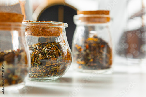 Fotografía  Glass jars with dry tea leaves close up on white table