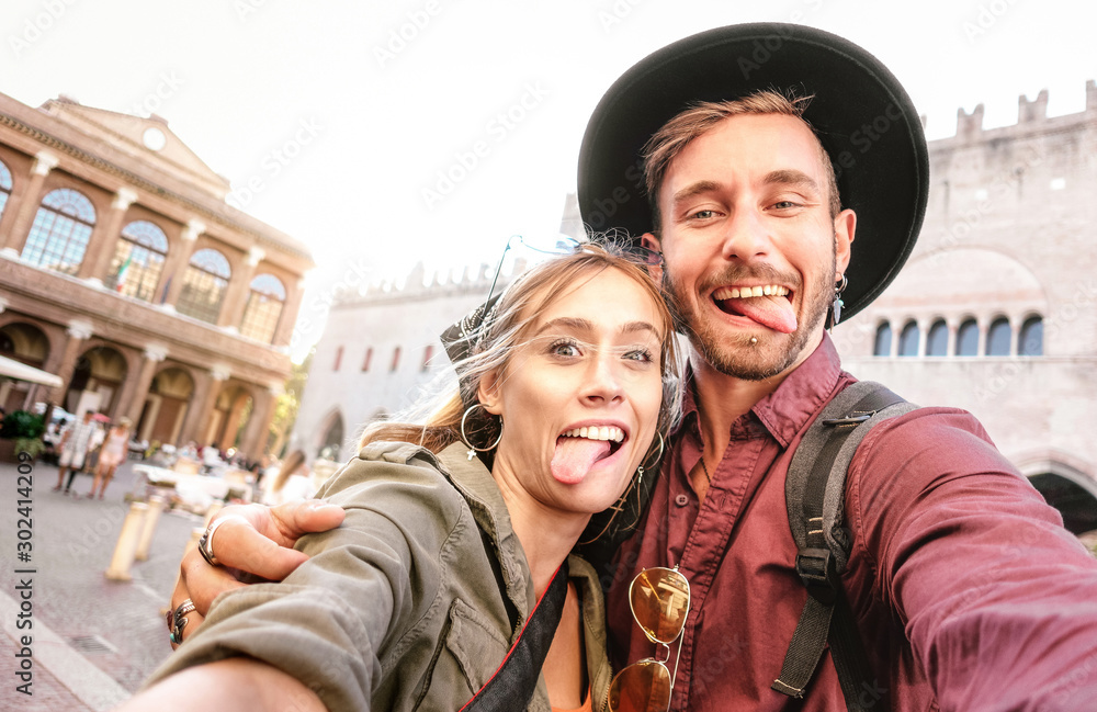 Fototapety, obrazy: Happy boyfriend and girlfriend in love having genuine fun taking selfie at old town tour - Wanderlust life style travel vacation concept with tourist couple on city sightseeing - Bright warm filter