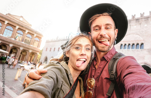 Fototapeta Happy boyfriend and girlfriend in love having genuine fun taking selfie at old town tour - Wanderlust life style travel vacation concept with tourist couple on city sightseeing - Bright warm filter obraz