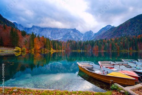 Obraz Alpine lake and colorful boats, Lake Fusine,Italy - fototapety do salonu