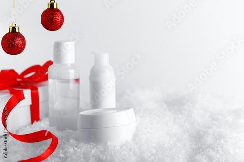 Obraz na plátně  Skincare cosmetics bottles on stylized snow covered surface
