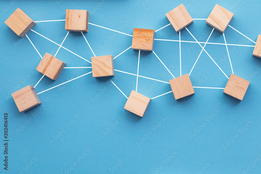 Fototapeta Wooden blocks connected together on a blue background. Teamwork concept