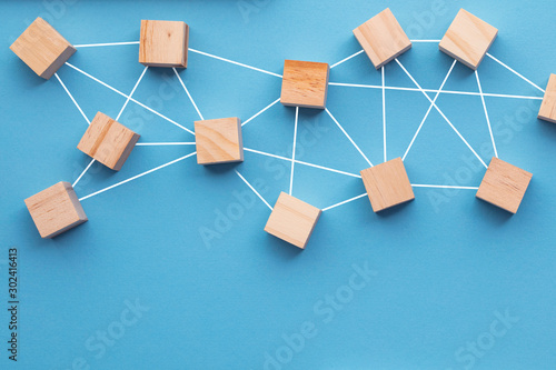 Fototapeta Wooden blocks connected together on a blue background. Teamwork concept obraz na płótnie