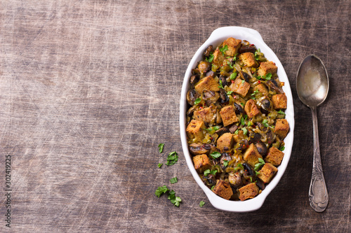 Tuinposter Brood Vegan Stuffing with Mushrooms, Leeks and crunchy croutons on wooden table, top view, horizontal. Thanksgiving traditional meal
