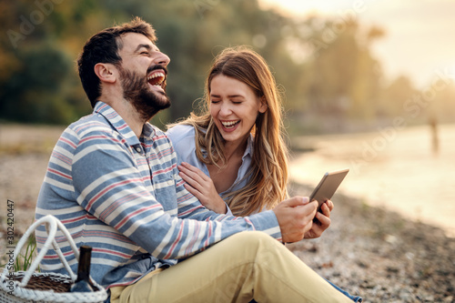 Leinwand Poster  happy laughing caucasian fashionable young couple sitting on coast near river and using tablet