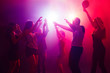 canvas print picture - Entertainment. A crowd of people in silhouette raises their hands on dancefloor on neon light background. Night life, club, music, dance, motion, youth. Purple-pink colors and moving girls and boys.