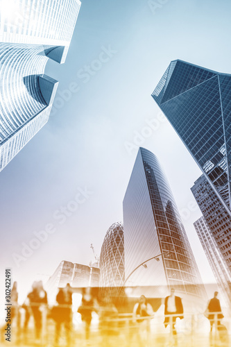 Silhouettes of people walking in the street near skyscrapers and modern office buildings in Paris business district. Multiple exposure image. Economy, finances, business concept illustration.