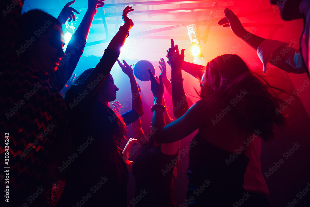 Fototapeta A crowd of people in silhouette raises their hands on dancefloor on neon light background. Night life, club, music, dance, motion, youth. Purple-pink colors and moving girls and boys.