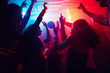 canvas print picture - A crowd of people in silhouette raises their hands on dancefloor on neon light background. Night life, club, music, dance, motion, youth. Purple-pink colors and moving girls and boys.
