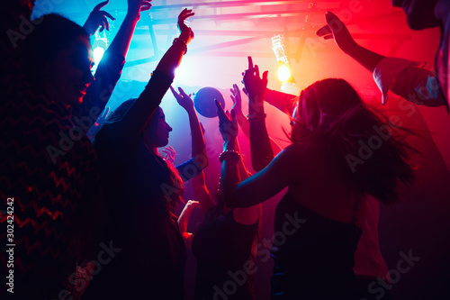 A crowd of people in silhouette raises their hands on dancefloor on neon light background. Night life, club, music, dance, motion, youth. Purple-pink colors and moving girls and boys.