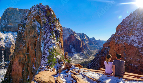 COPY SPACE: Young couple sits atop Angel's Landing and observes the canyon Wallpaper Mural