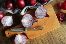 Red Onions On Wooden Chopping Cutting Board On Textile Napkin Over Dark Wooden Rustic Texture Background. Top View, Space For Text