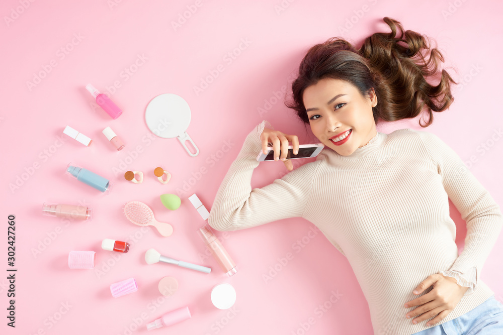 Fototapeta Young Asian beautiful woman show smart phone with her cosmetic makeup tools - she is lying on the pink floor. Top view