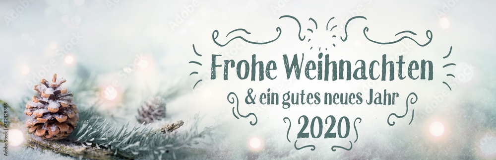 Fototapeta Christmas greetings  2019  2020  -  German language  -  Merry Christmas and Happy New Year  -  Fir branch in sn ow landscape with magic lights
