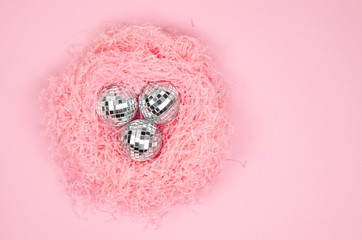 Closeup flat lay pink paper filler nest shape with silver glass Christmas balls on a pink background. Top view frame female winter holidays concept