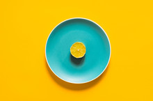 A Slice Of Fresh Lime Lying On Color Plate On Yellow Background. Concept Of Vegan Diet And Citrus Food.