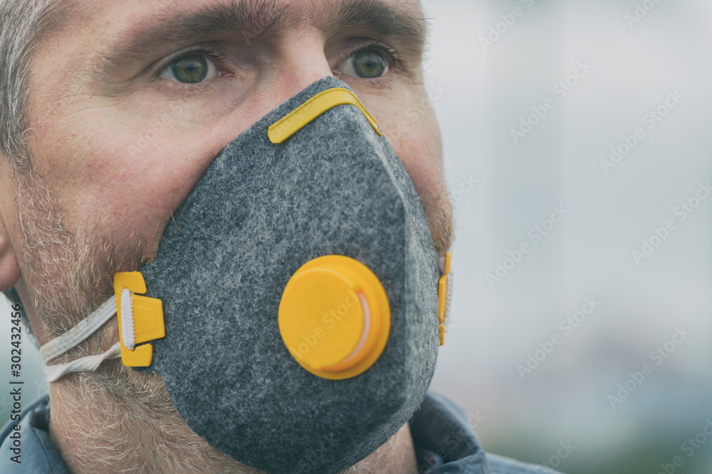 Fototapety, obrazy: wearing a real anti-pollution, anti-smog and viruses face mask