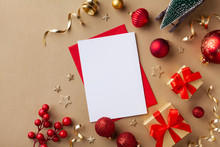 Empty Paper Blank For Christmas Or New Year Greeting Card. Gift Boxes, Holiday Decorations, Small Fir Tree On Golden Background Top View. Flat Lay.